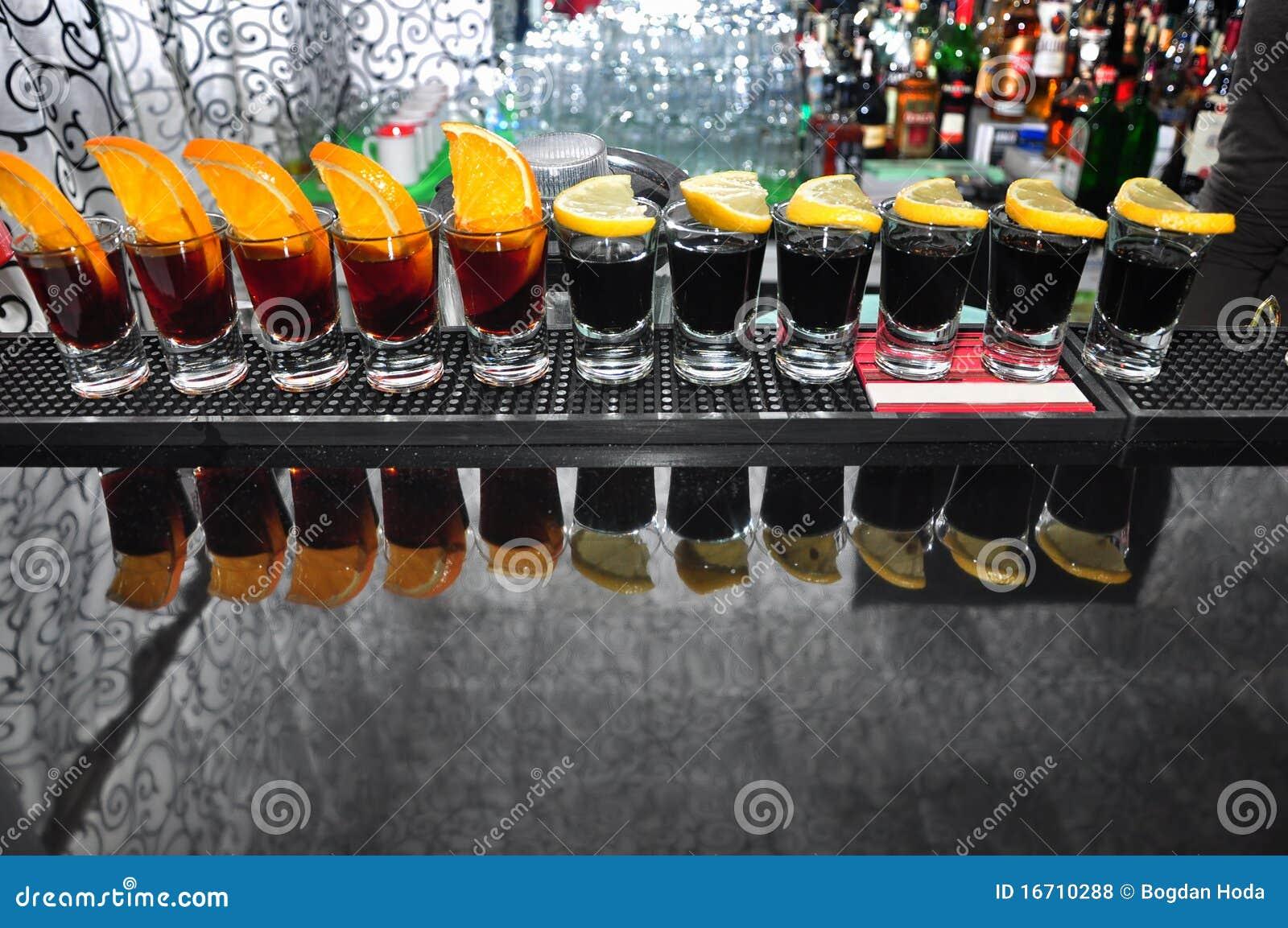 Fila de cuatro bebidas de vodka negra en la barra