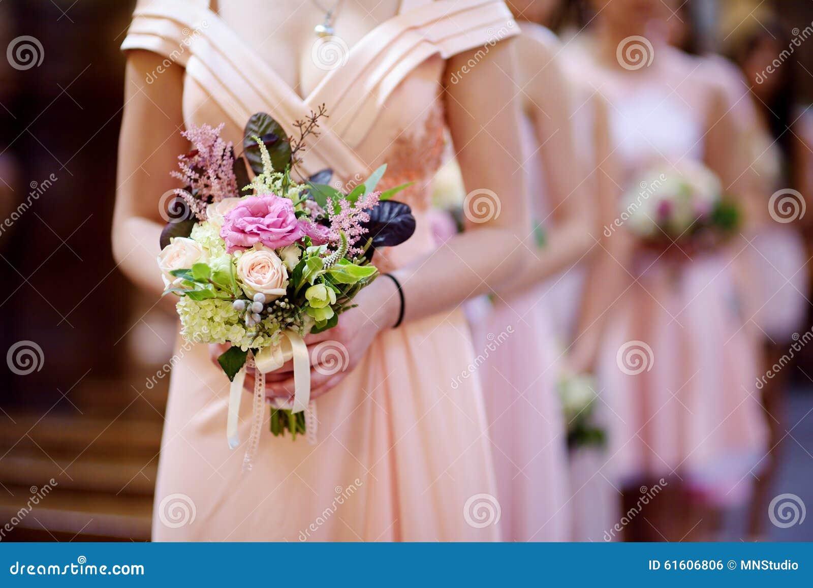 Fila de damas de honor con los ramos en la boda