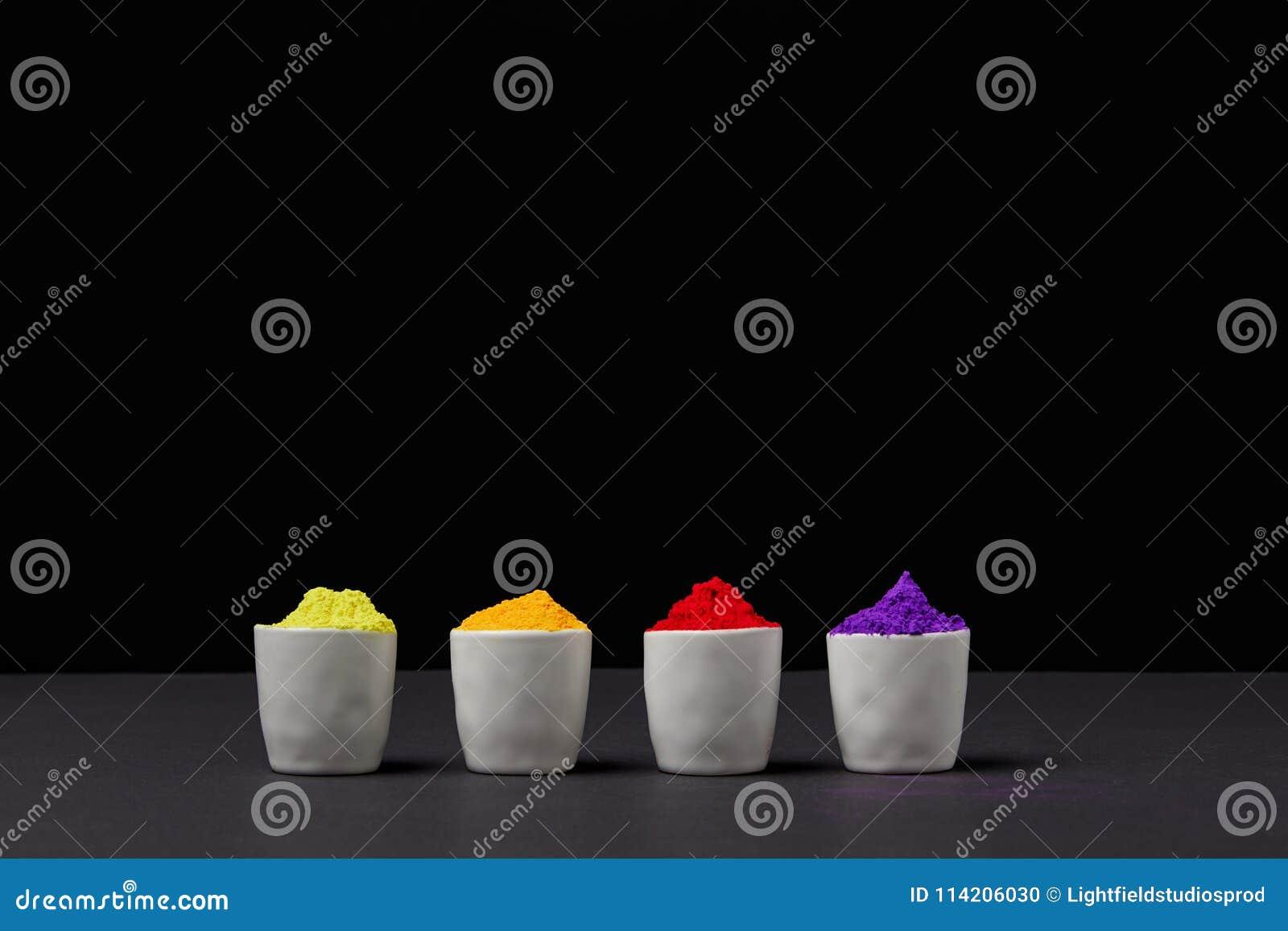 Fila de la pintura colorida del holi en cuatro cuencos en negro