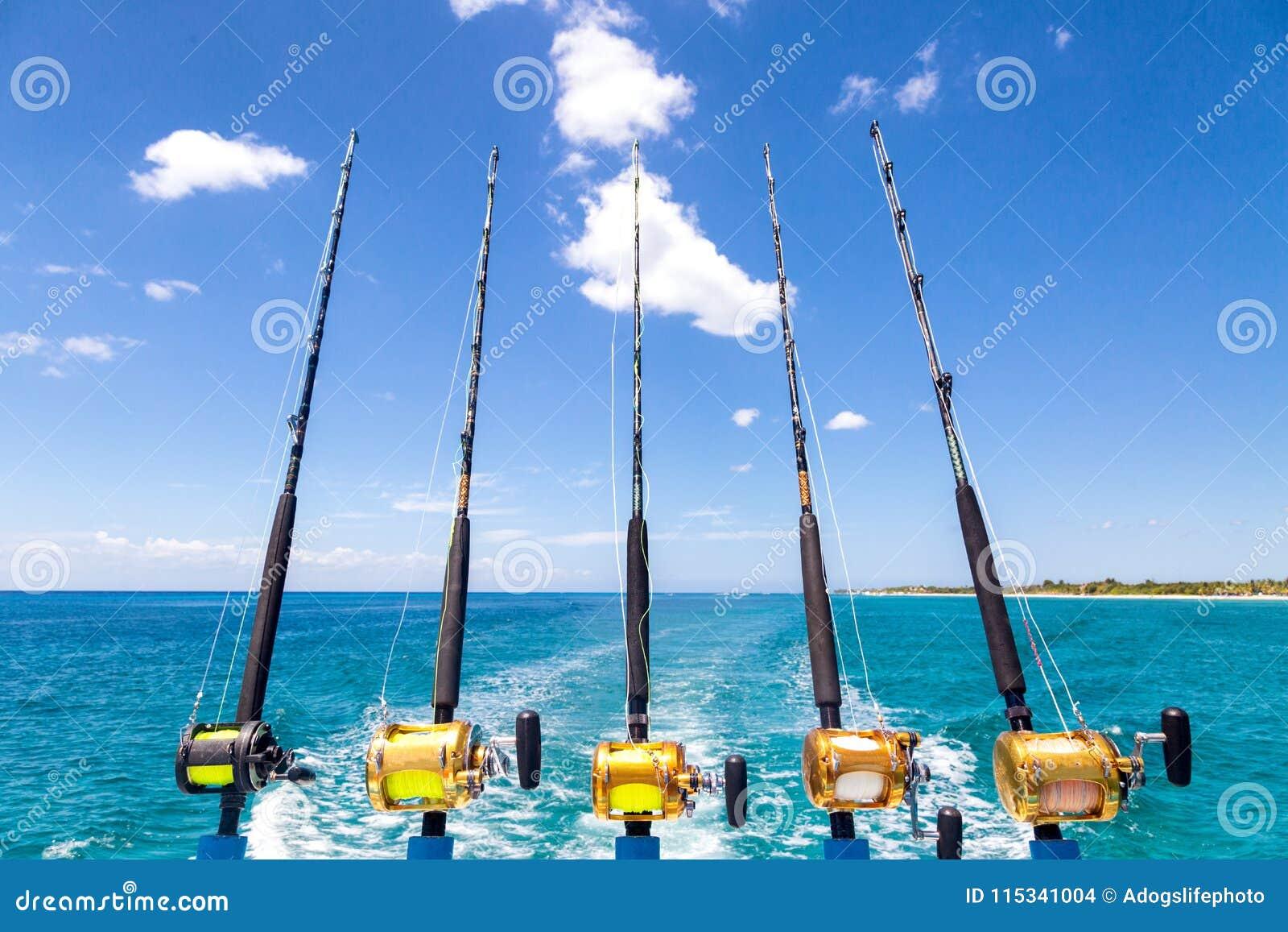 Fila de las cañas de pescar del mar profundo en el barco