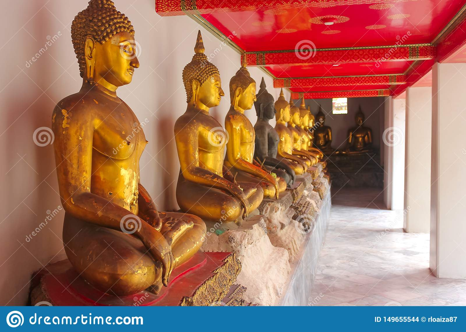 Fila de las estatuas de oro de Buda en Wat Phra Kae, templo de Emerald Buddha, Bangkok, Tailandia