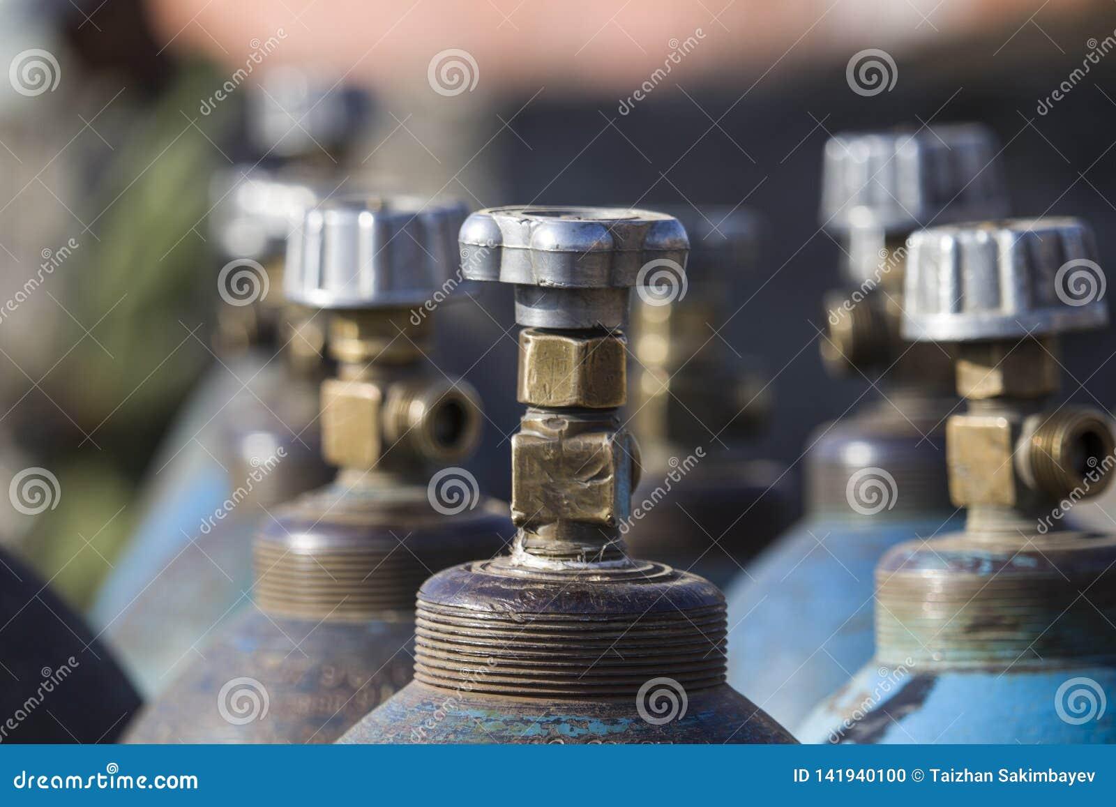 Fila de los envases industriales licuados del gas del oxígeno con las válvulas Ciérrese para arriba de válvulas