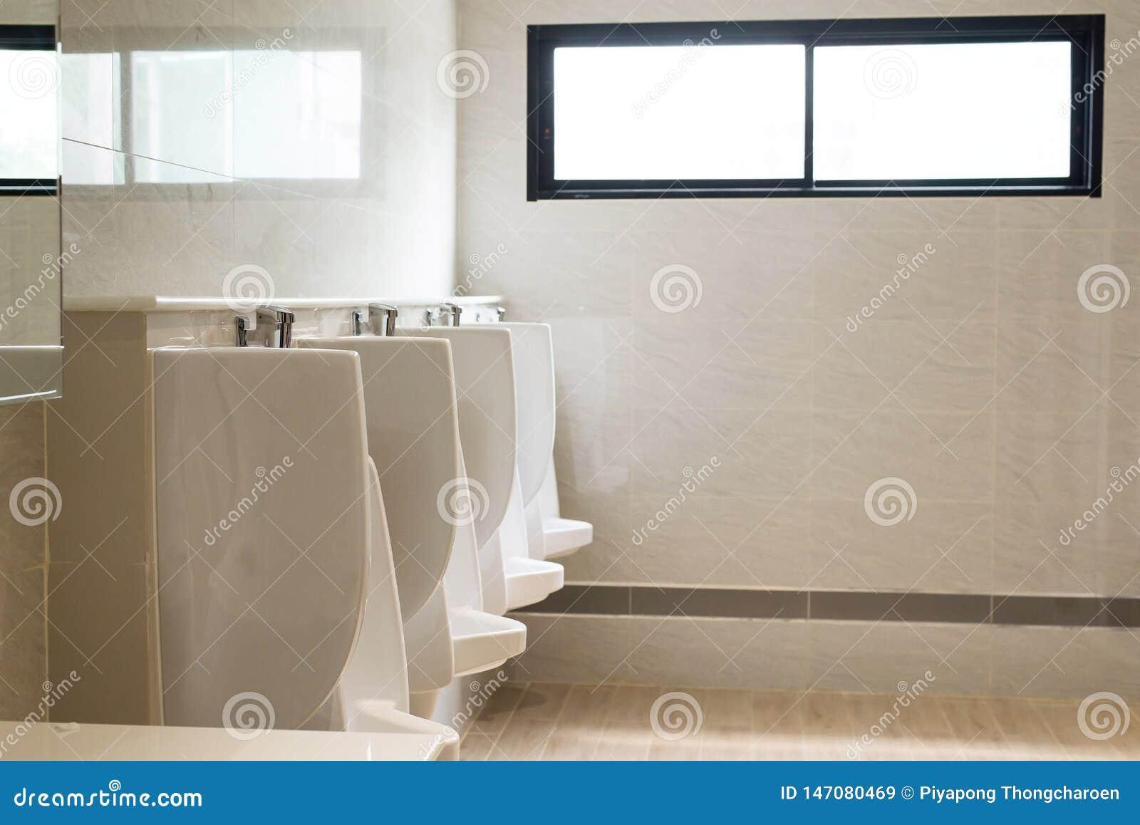 Fila degli orinali bianchi dell interno per l uomo nella toilette, lavabo di lusso moderno di progettazione