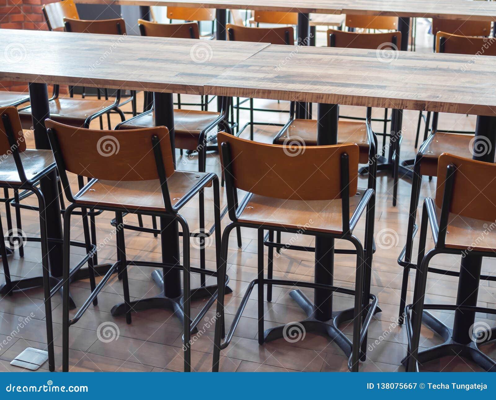 Fila degli sgabelli da bar di legno e della tavola di legno immagine