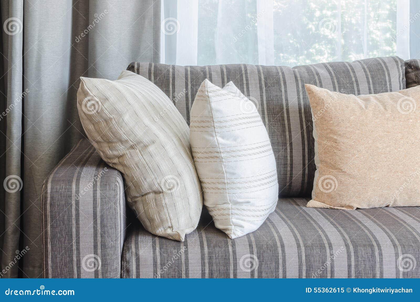 Fila dei cuscini sul sofà grigio moderno