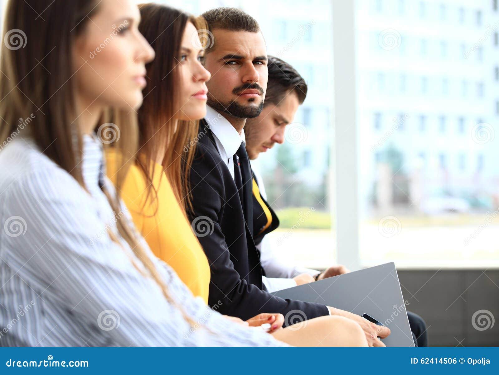 Fila della gente di affari che fa le note al seminario