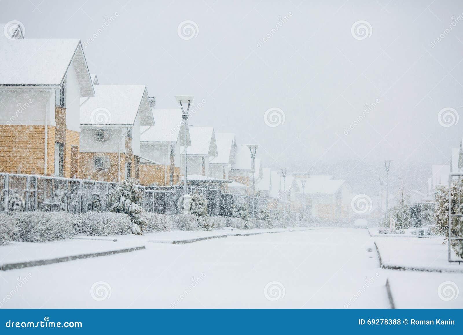 Fila delle case isolate dalla neve, case con il marciapiede sulla st vuota