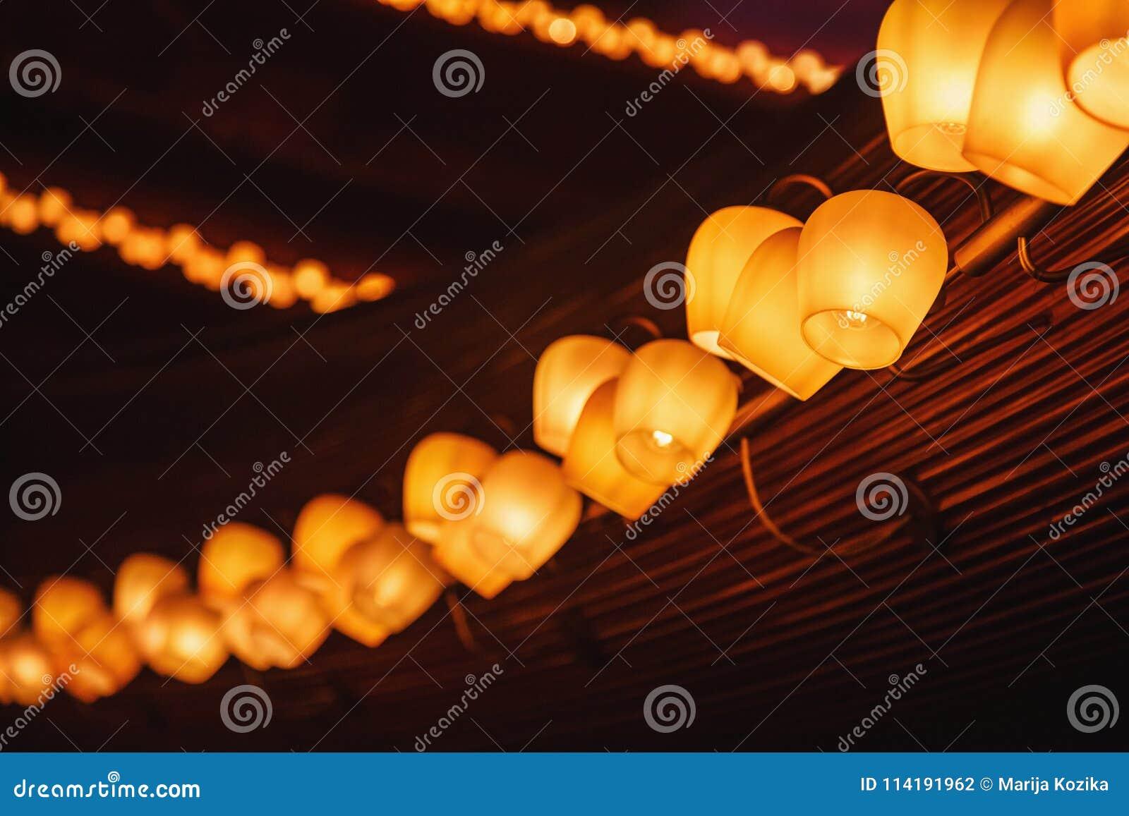 Fila larga de las lámparas del tungsteno en un panel de madera