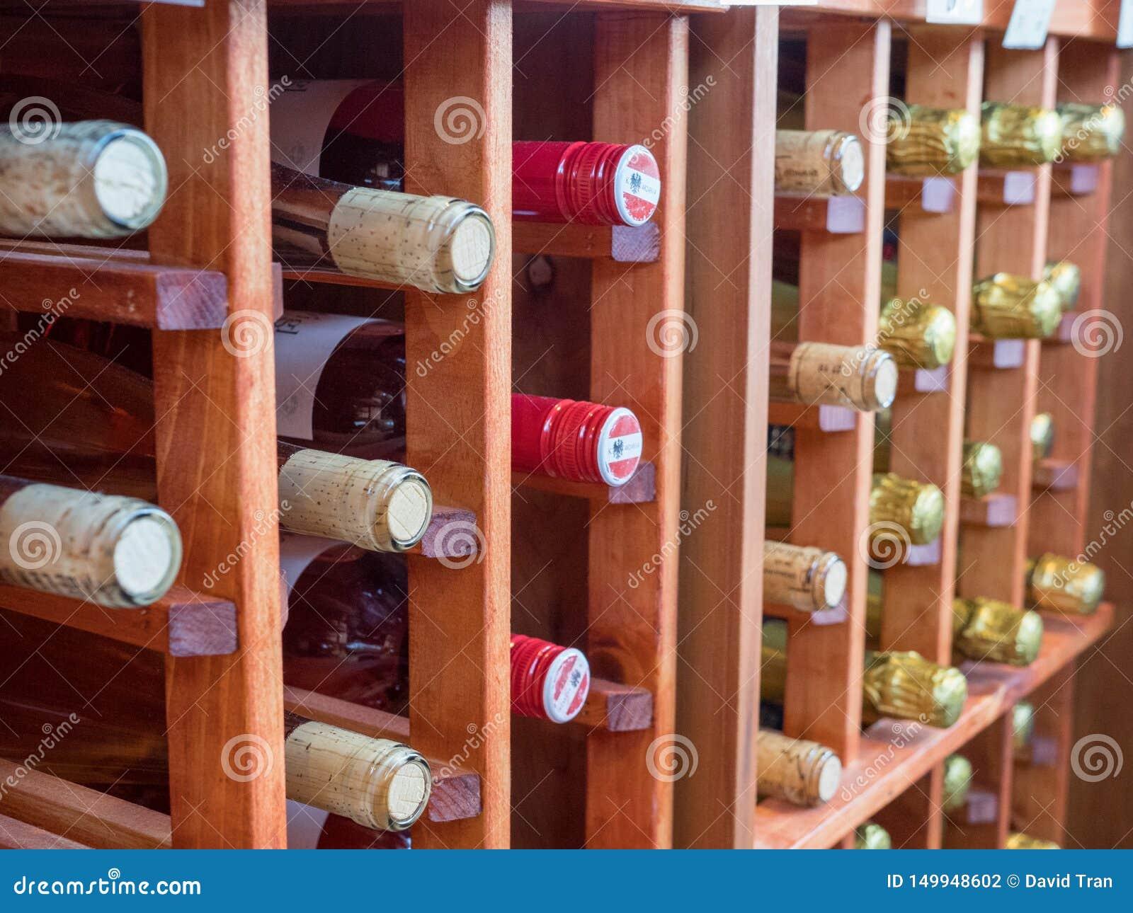 Filas de las botellas de vinos blancos rojos y en el estante de madera del vino