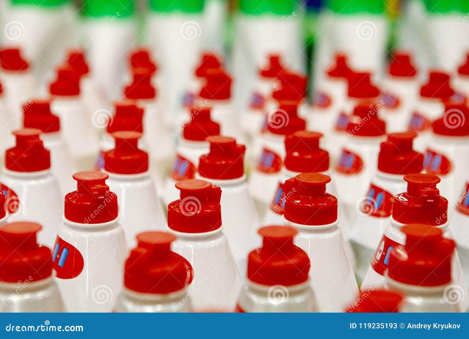 Filas rectas de corchos rojos brillantes en las botellas