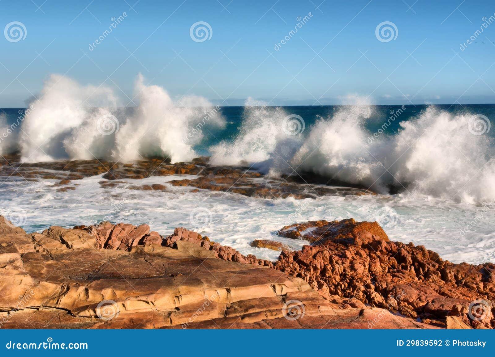 A fileira da onda espirra na praia vermelha da rocha