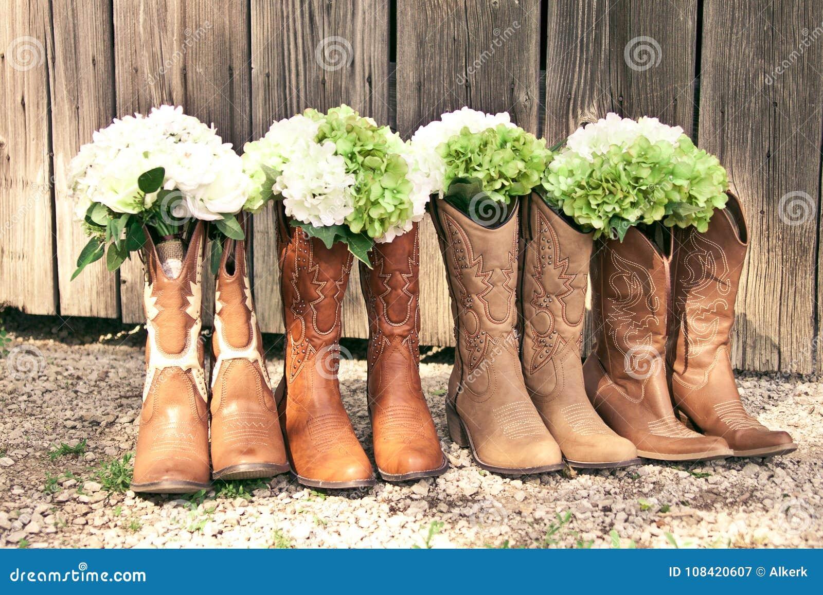 Fileira de botas e de ramalhetes de vaqueiro em um casamento do tema do país
