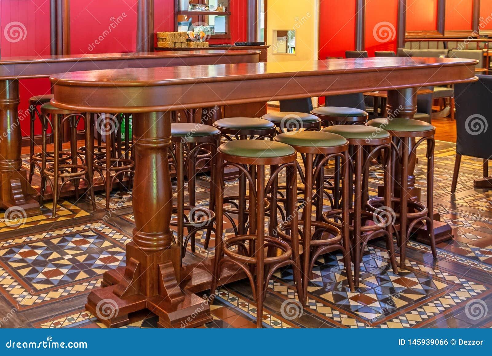 Fileira de cadeiras altas de madeira em uma barra na frente de uma tabela em um bar