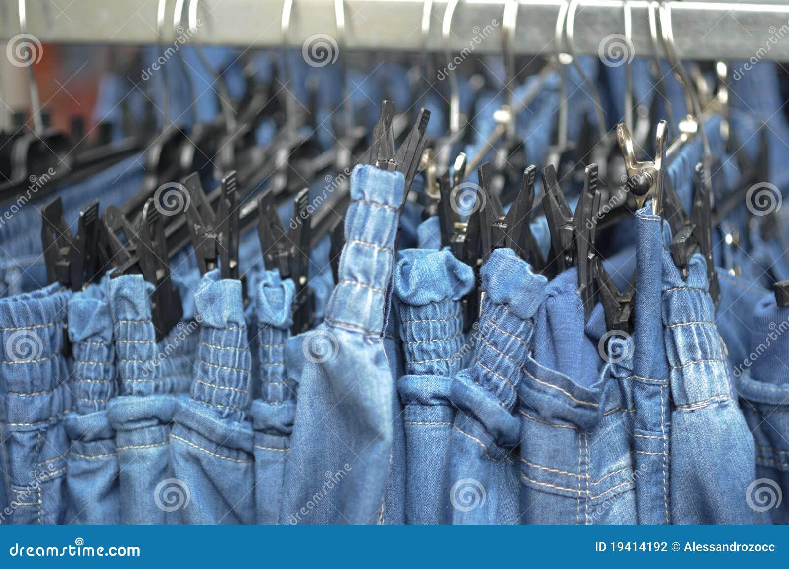 Fileira de calças das calças de brim no sell