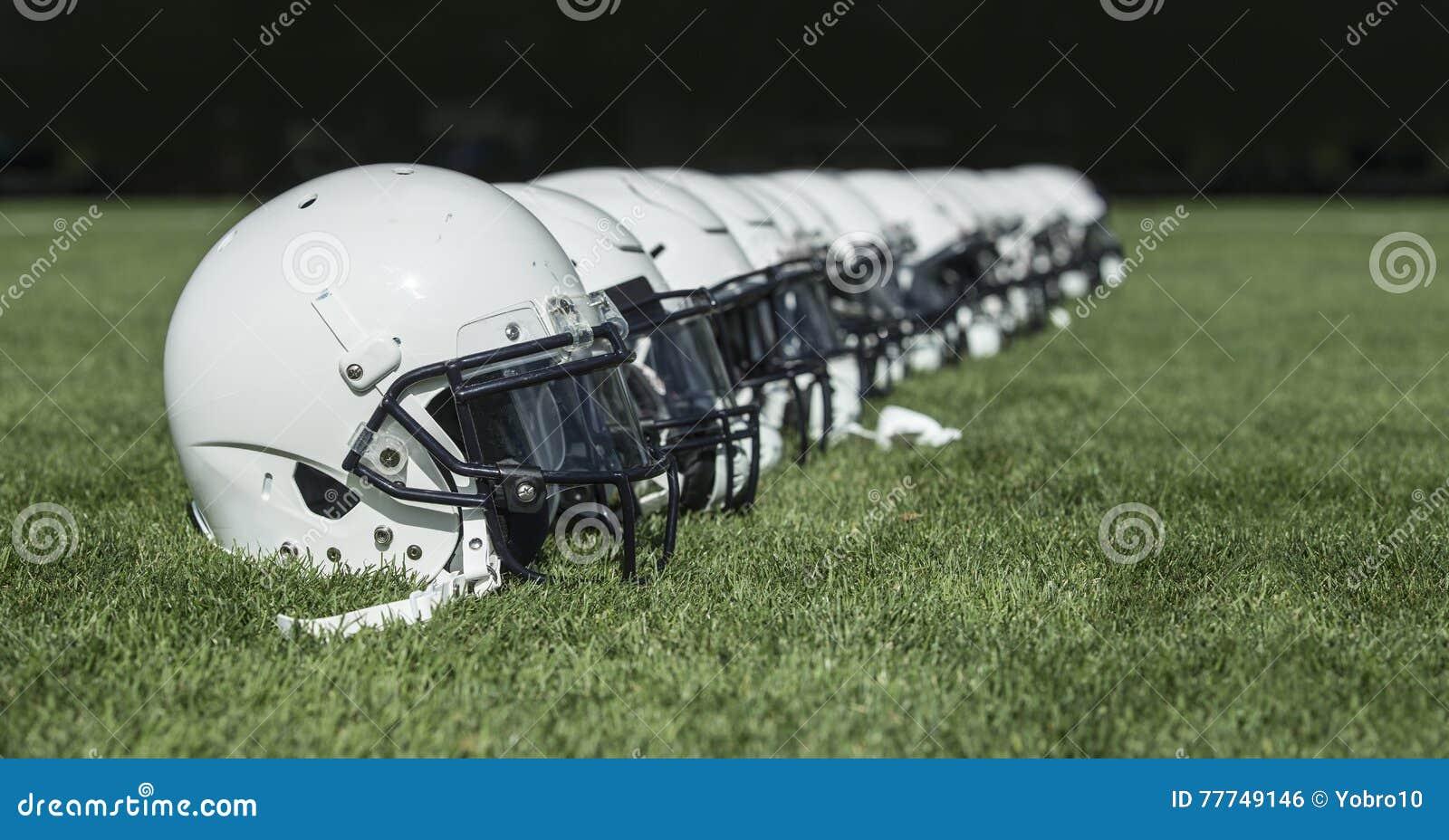 Fileira de capacetes de futebol americano antes de um jogo