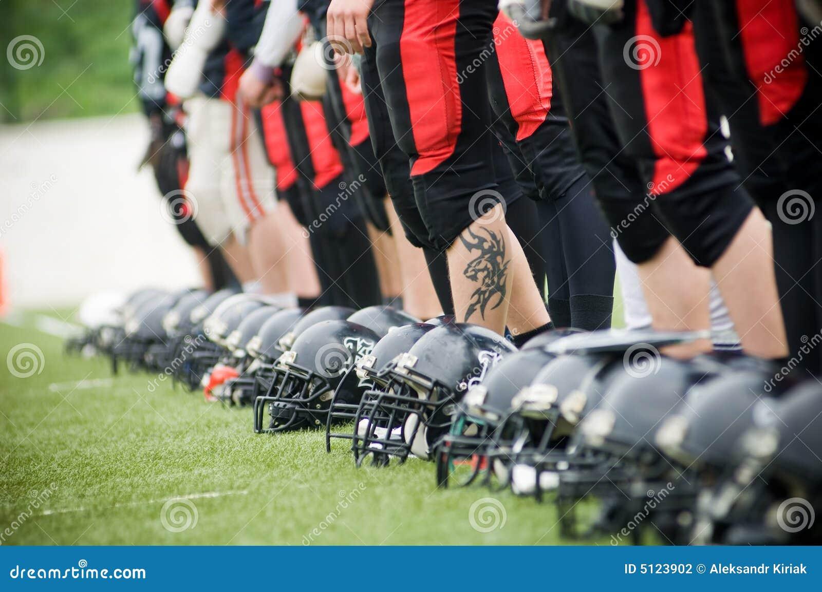 Fileira de capacetes e de pés de futebol