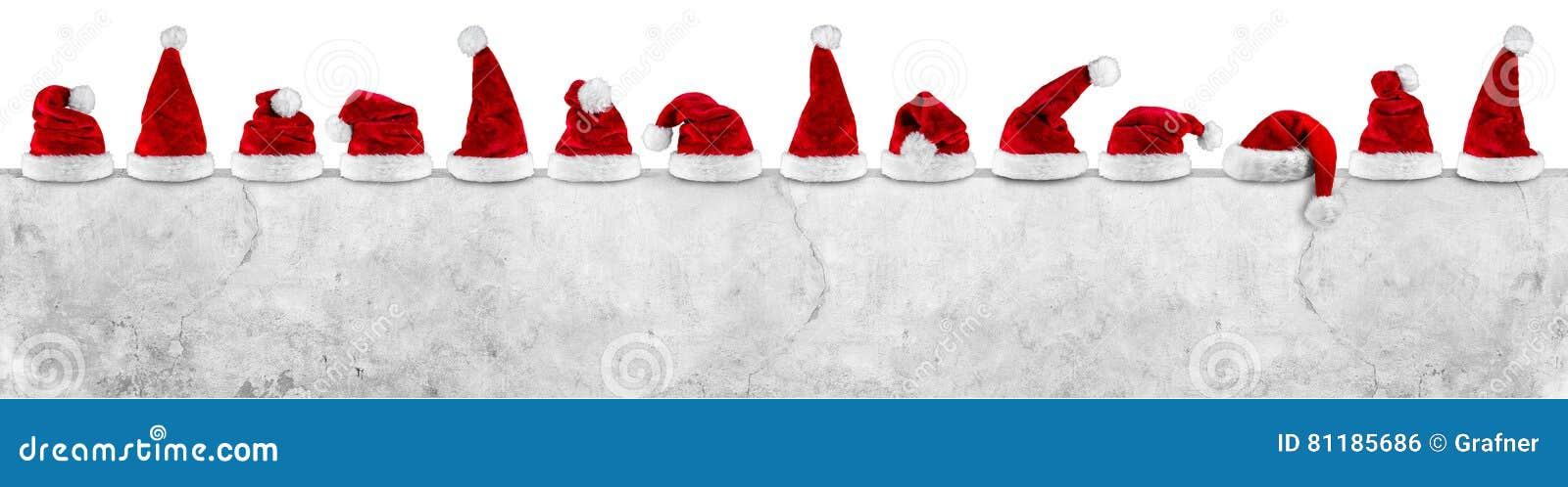 Fileira do chapéu branco vermelho do xmas do Natal de Papai Noel no concret vazio