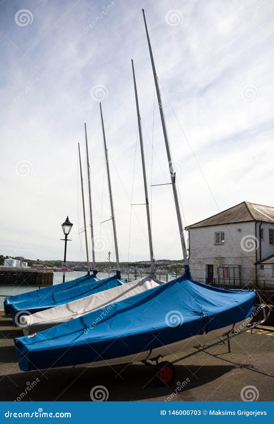Fileira dos barcos no armazenamento sob o toldo, armazém no cais do barco, Plymouth, Devon, Reino Unido, o 23 de maio de 2018