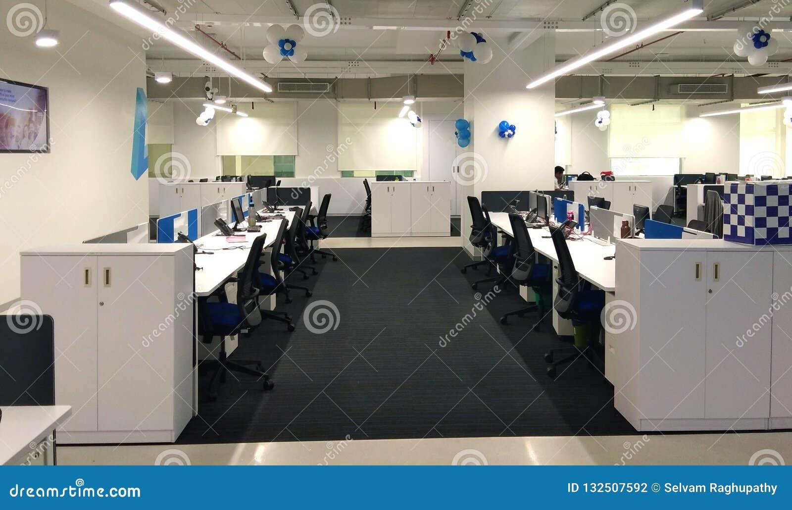 Fileira e computadores da cadeira na estação de trabalho uma empresa da tecnologia da informação