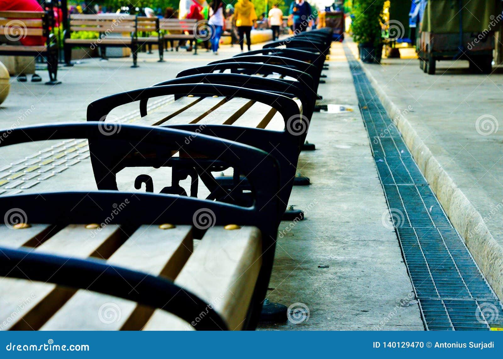 Fileiras da cadeira da madeira e do metal na rua da compra do ar livre em 3Sudeste Asiático