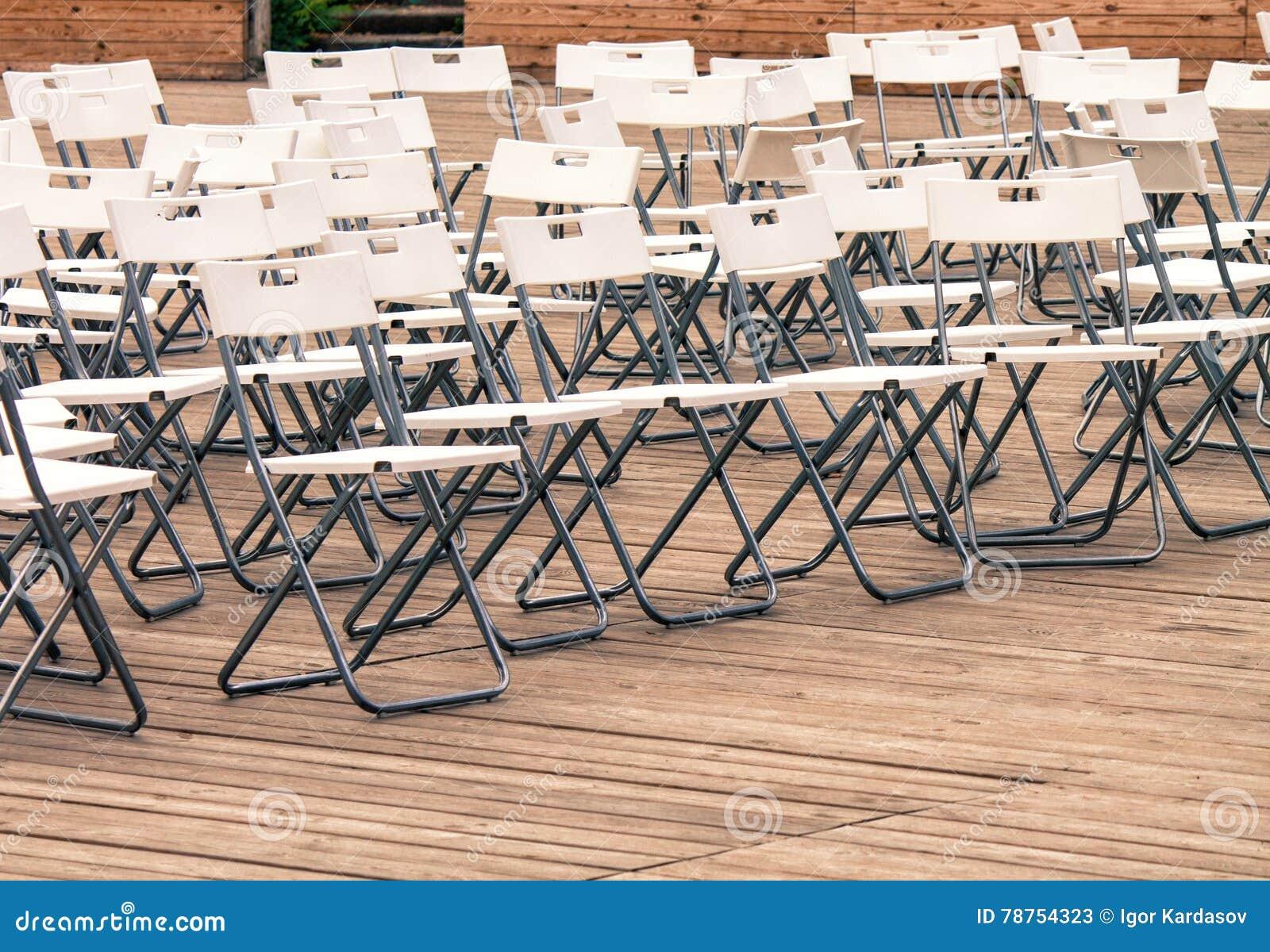 Fileiras de cadeiras modernas brancas vazias no assoalho de madeira do teatro