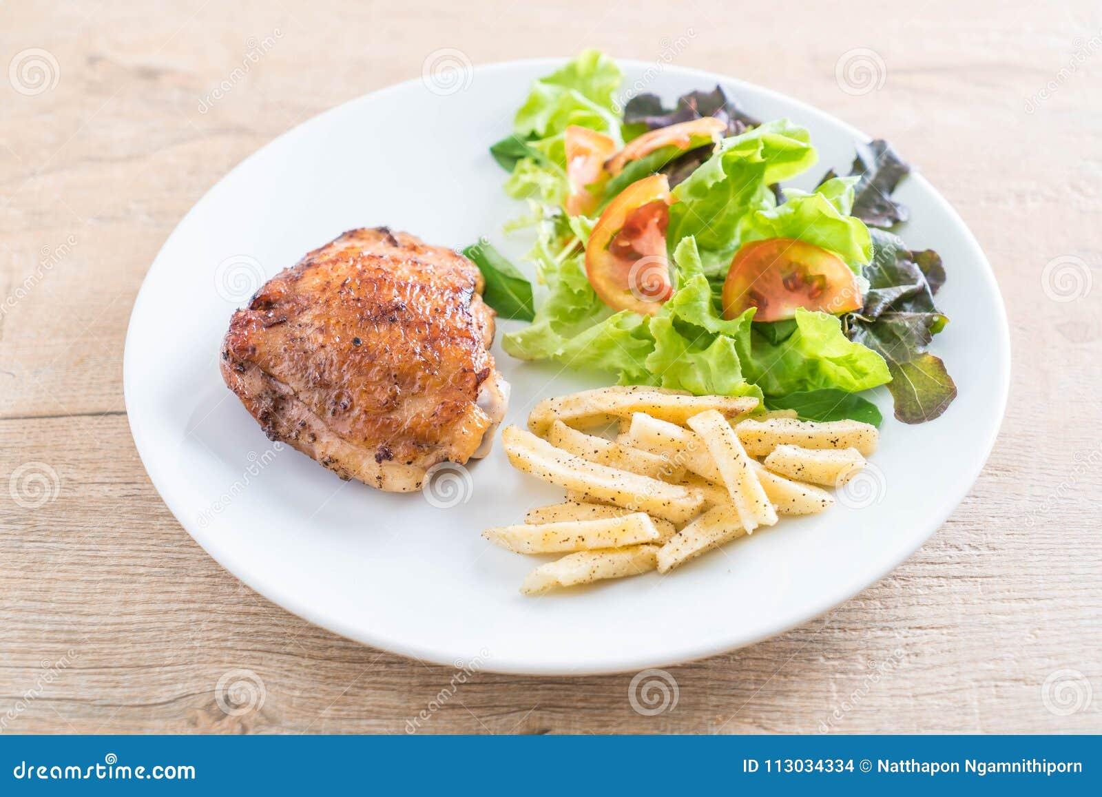 Filete asado a la parrilla del pollo con las patatas fritas y la ensalada vegetal