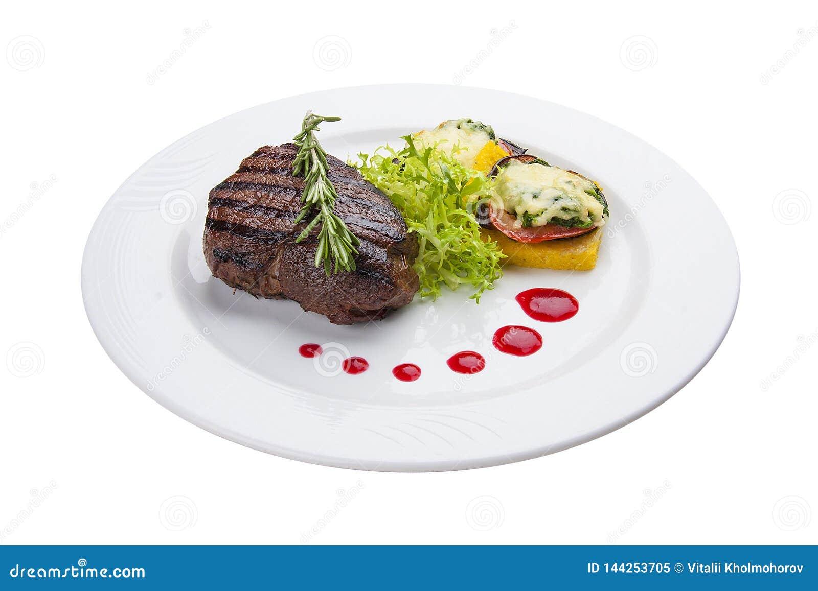 Filete de carne de vaca con verduras asadas a la parrilla y una tortilla En una placa blanca