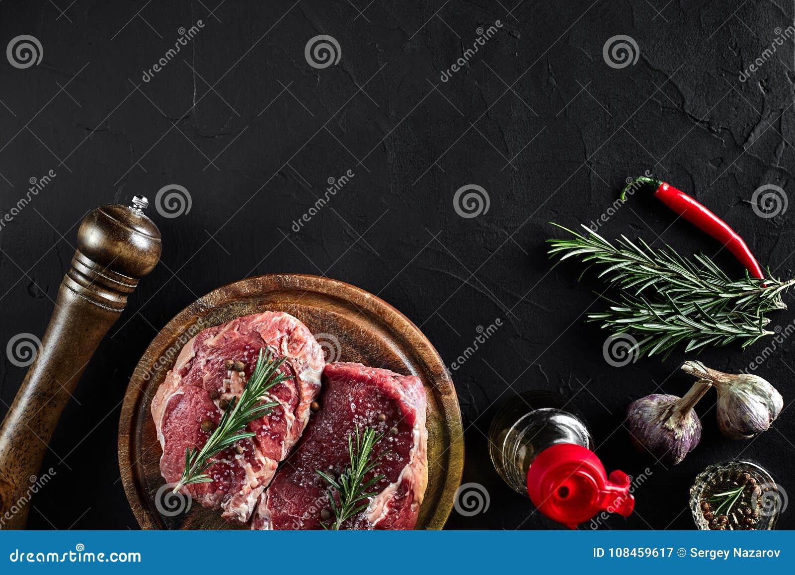 Filete de carne de vaca crudo con las especias y los ingredientes para cocinar en fondo de la tabla de cortar y de la pizarra Vis