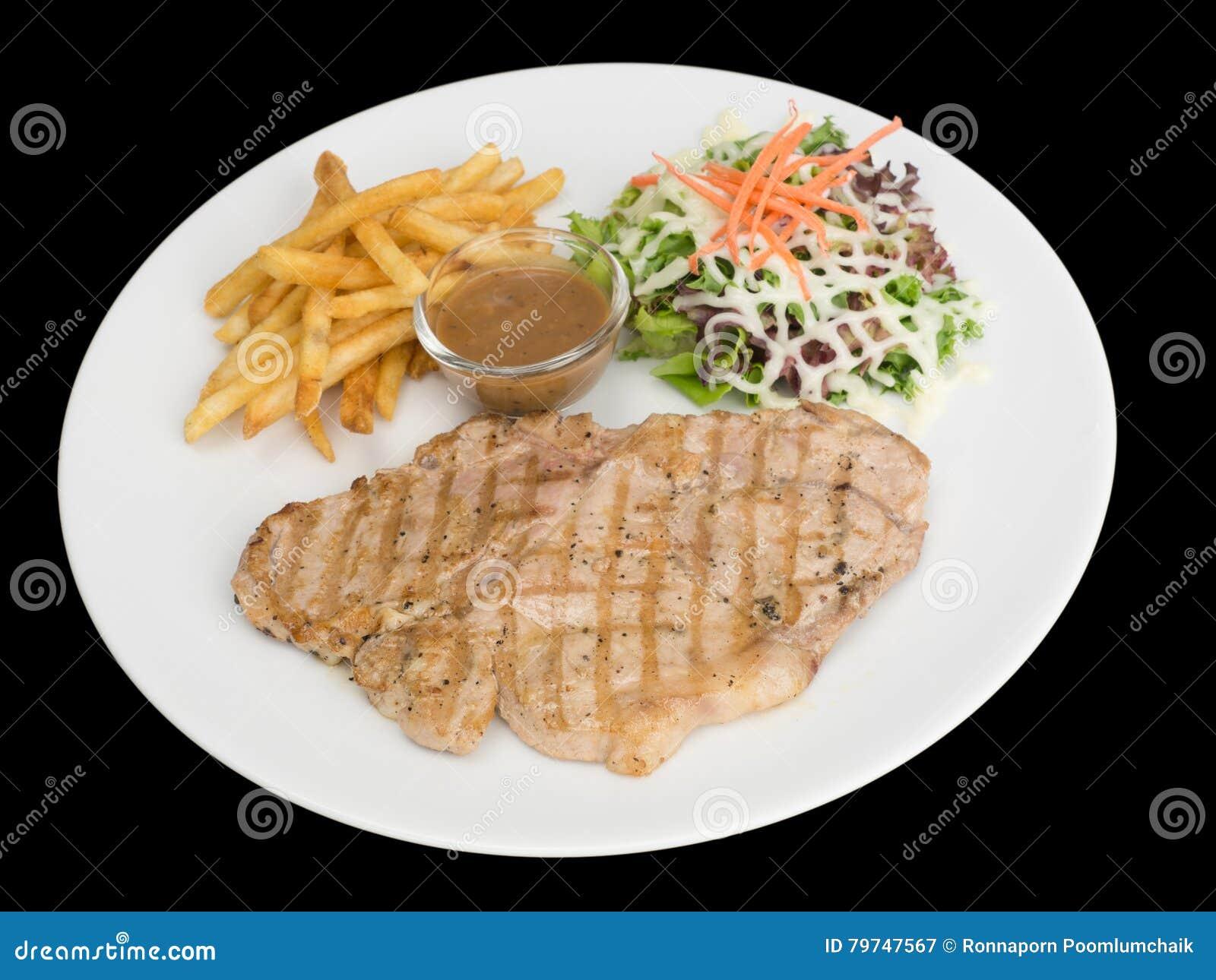 Filete de chuleta de cerdo con las patatas fritas, el pan y la verdura aislados