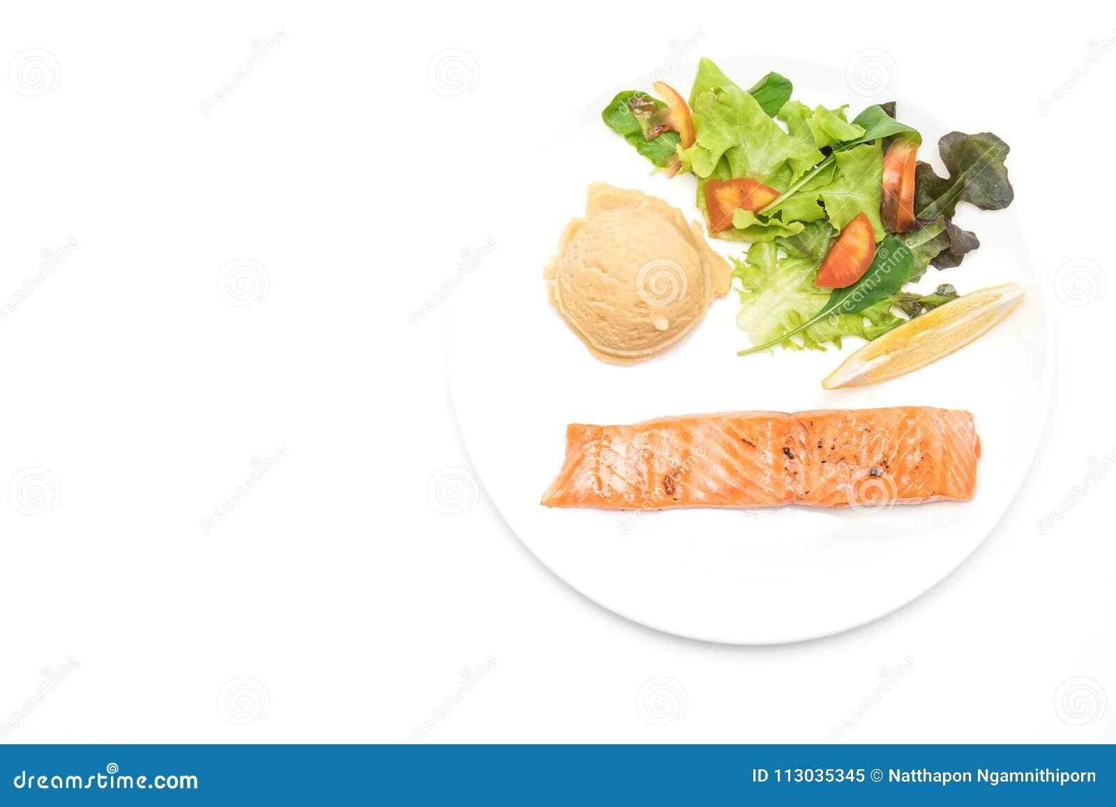 Filete de color salmón asado a la parrilla con la patata de puré y la ensalada de la verdura