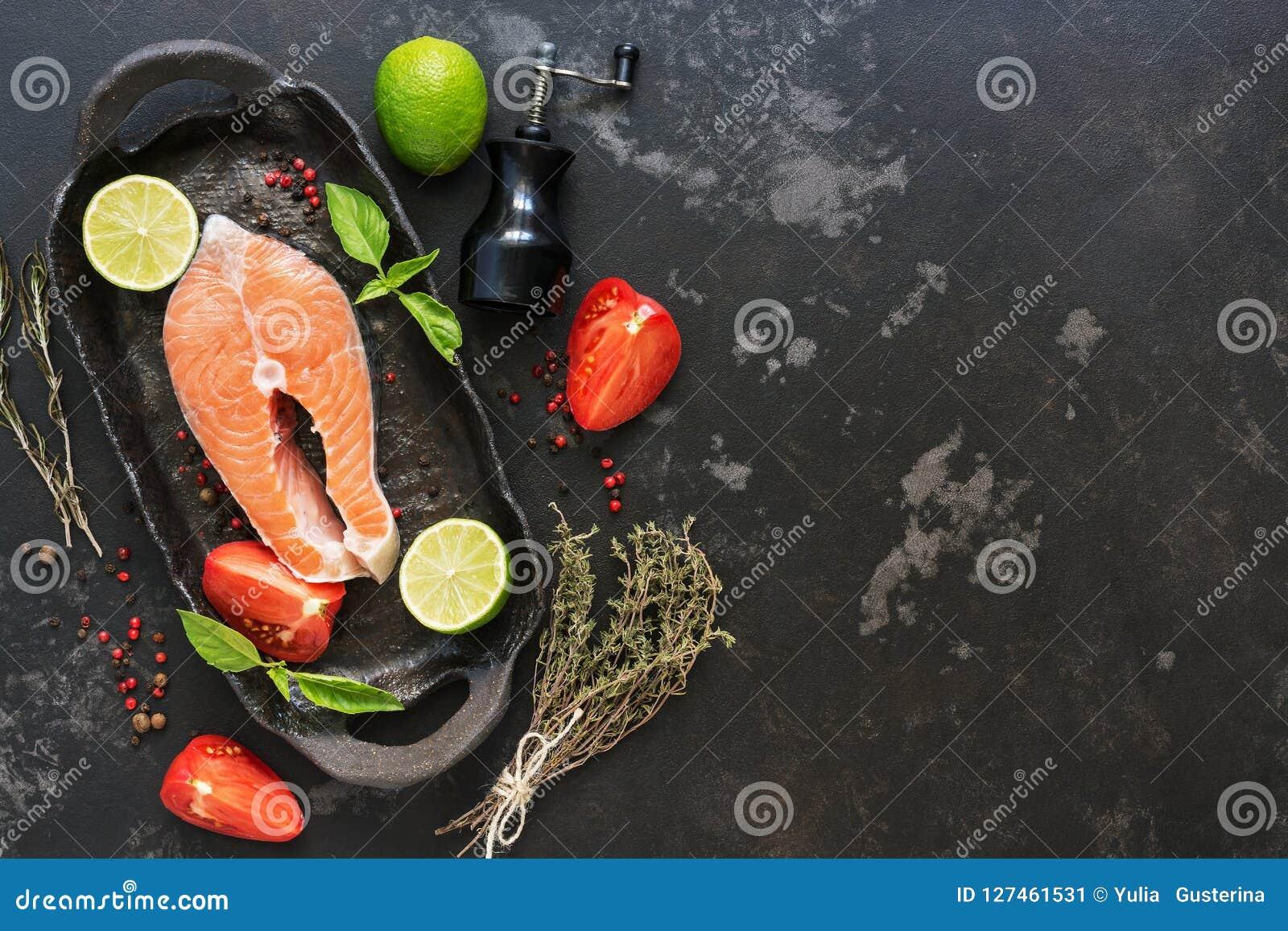 Filete de color salmón crudo con los ingredientes para cocinar en un fondo de piedra negro Visión superior, espacio de la copia