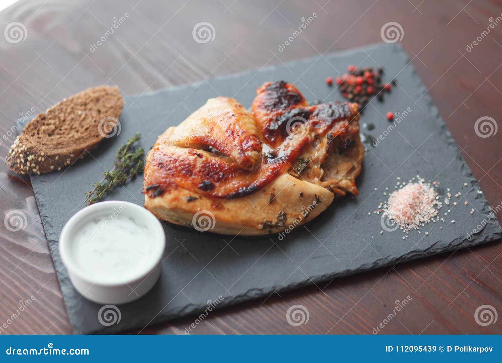 Filete del pollo frito con el souce y especia en tablero negro de la pizarra Foco selectivo
