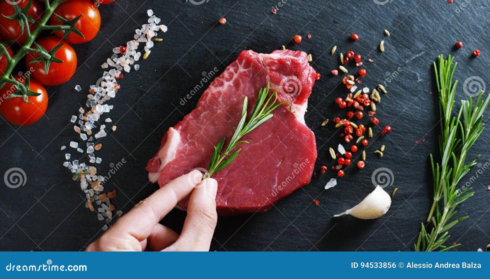 Filete jugoso hermoso de la carne fresca en una tabla con la sal, el romero, el ajo, y el tomate en un fondo negro, visión superi