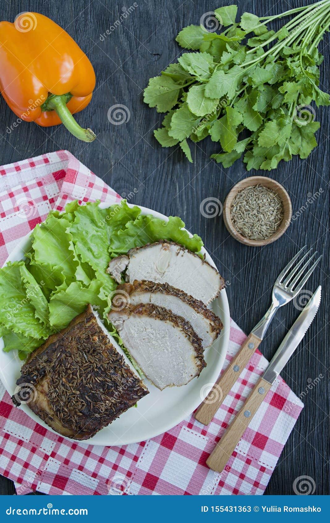 Filetto di carne di maiale al forno in spezie affettate su un piatto bianco con insalata verde Priorit? bassa di legno scura