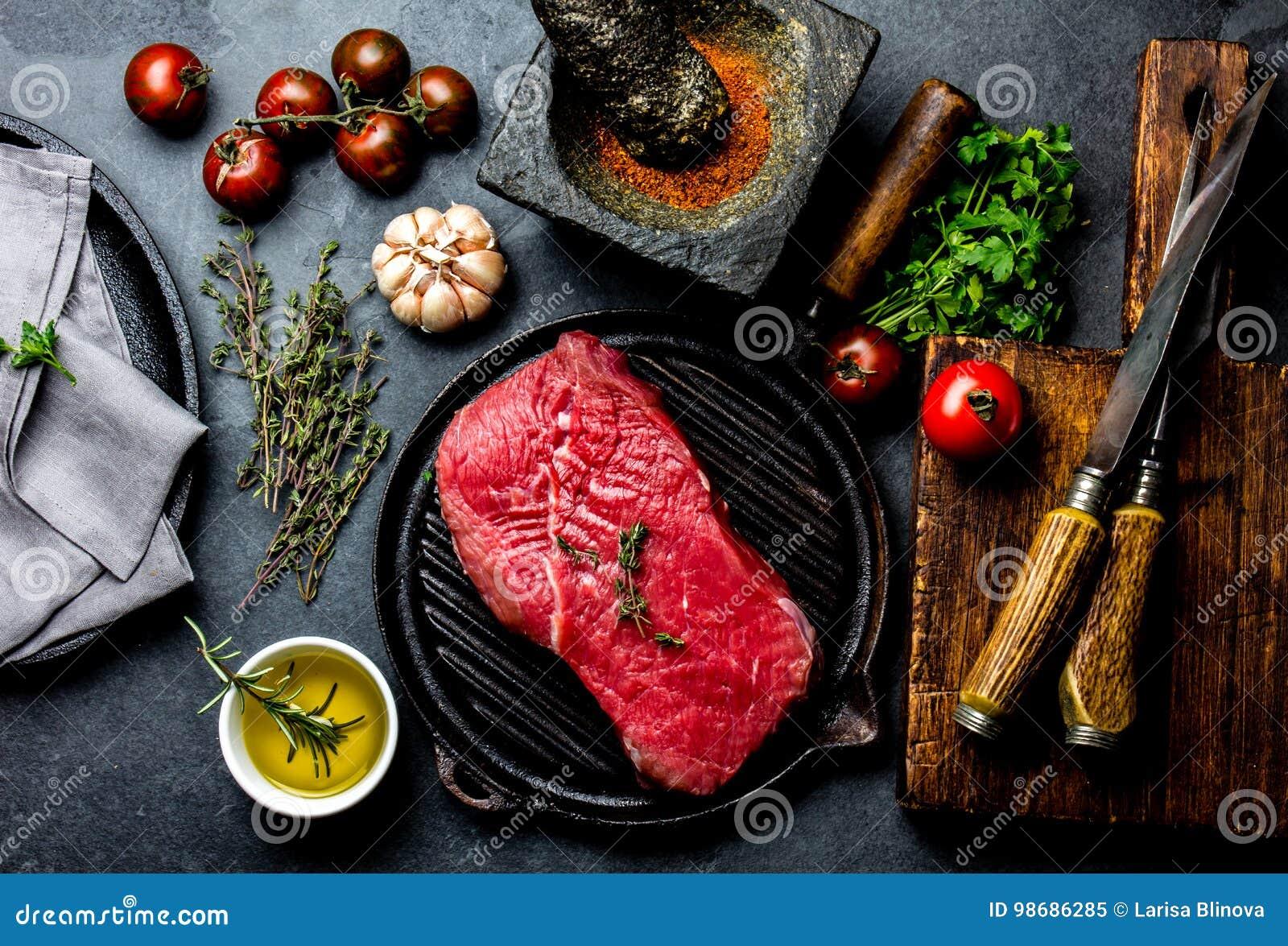 Filetto, erbe e spezie freschi di manzo della bistecca della carne cruda intorno al tagliere Alimento che cucina fondo con lo spa