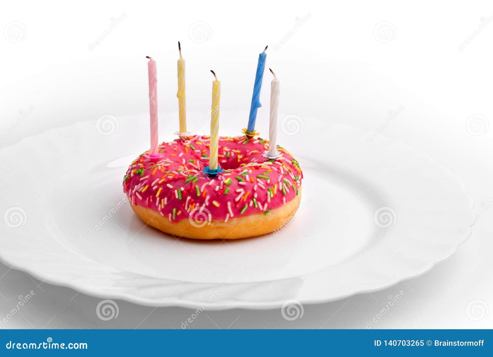 Filhós cor-de-rosa na placa branca como o bolo de aniversário com velas no fundo branco