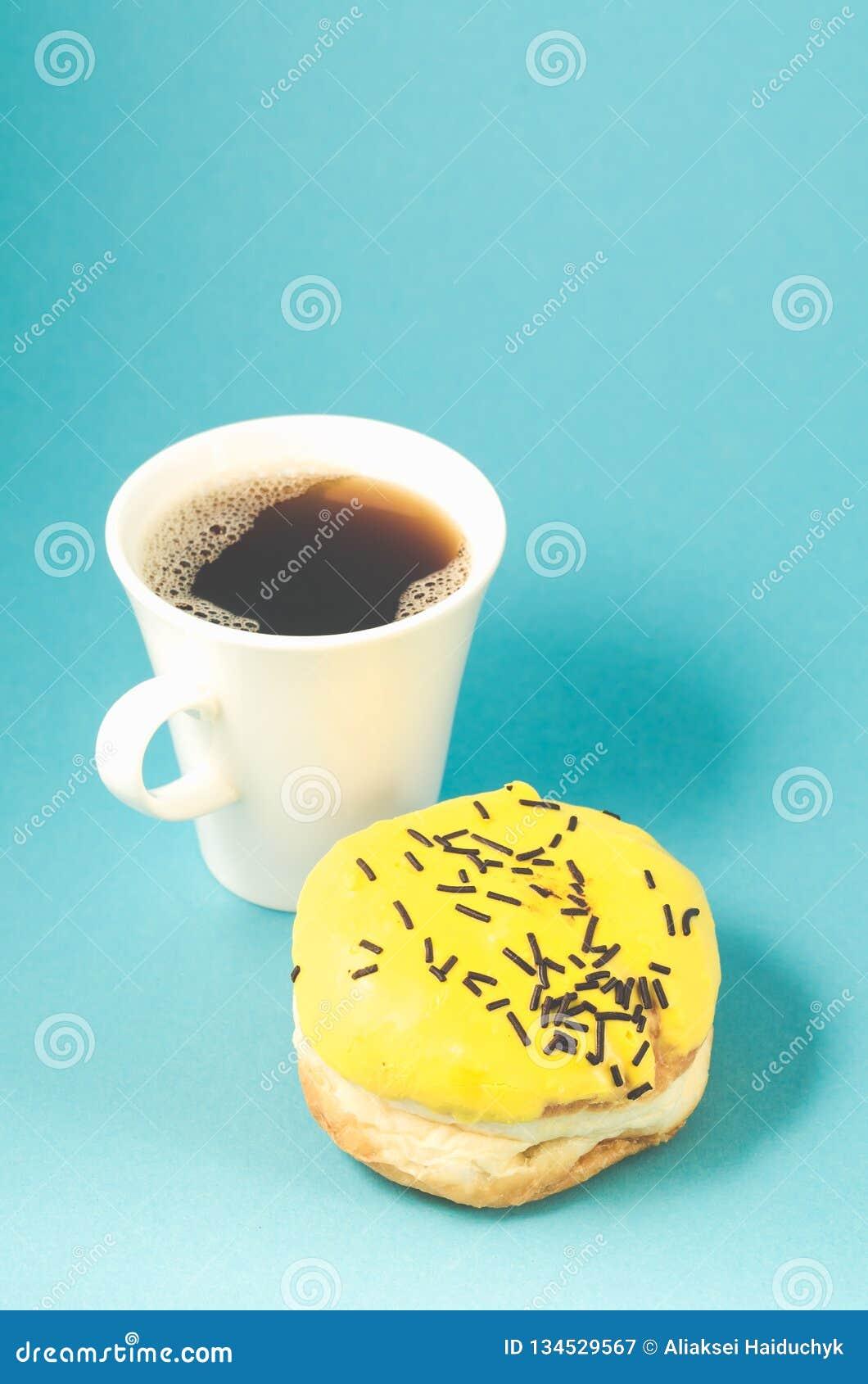 Filhós e copo do coffe isolado no fundo azul /Donut no esmalte amarelo e copo branco do coffe no fundo azul