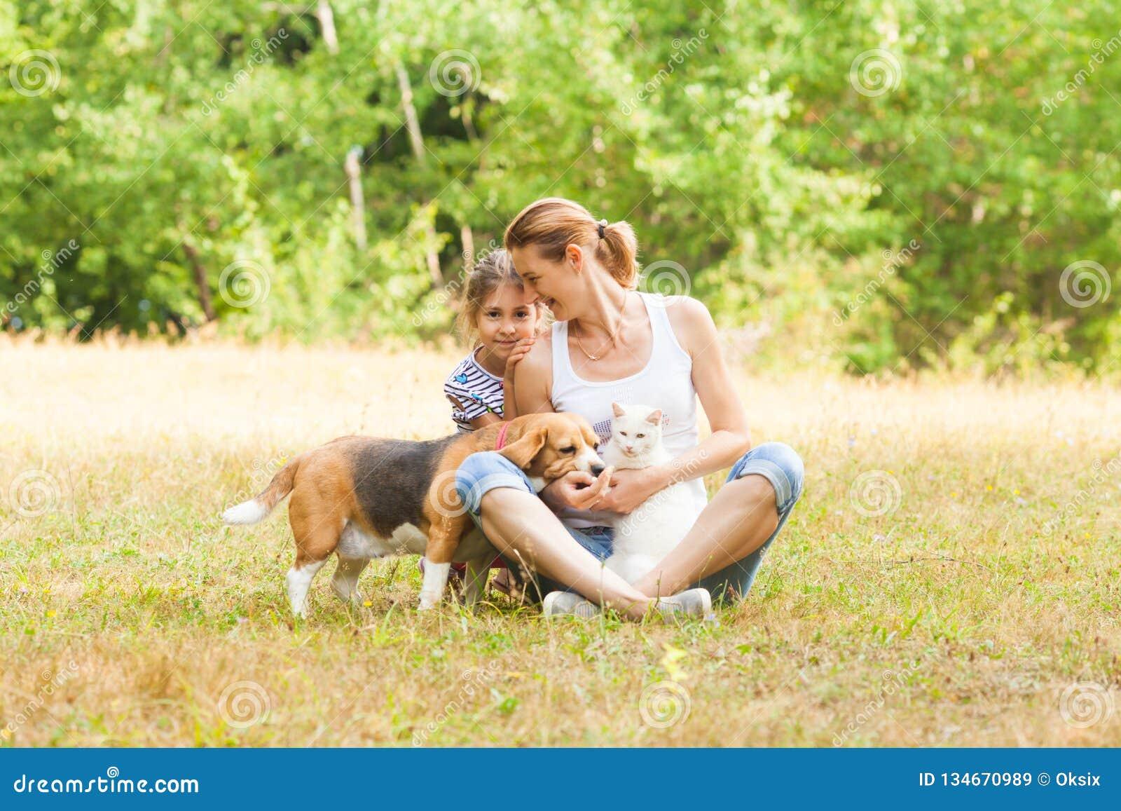 Filha adorável e mamã dos pares que sentam-se em uma grama com seus animais de estimação