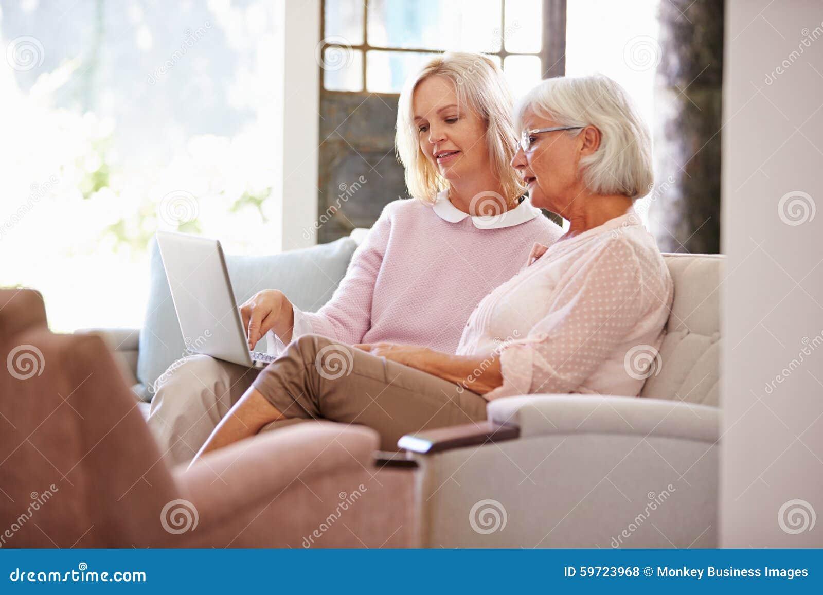 Filha adulta que ajuda a mãe superior com computador em casa