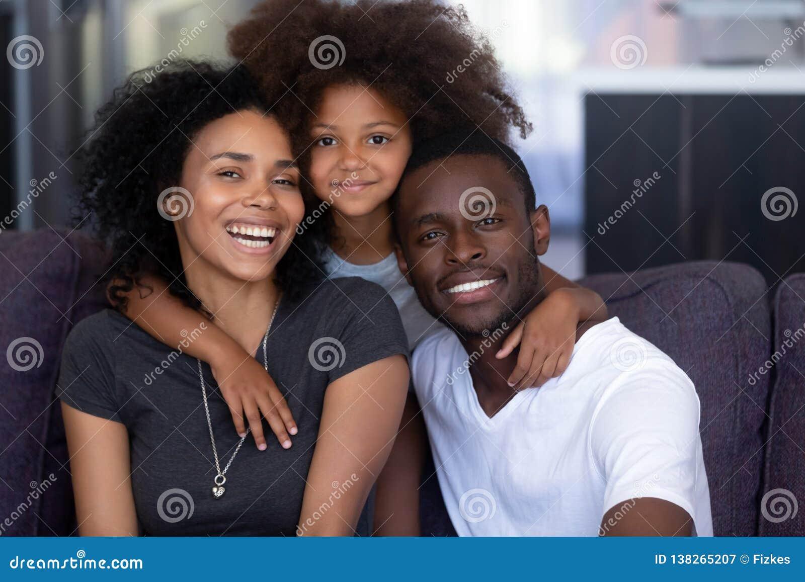 Filha africana da criança que abraça pais pretos de amor novos, retrato