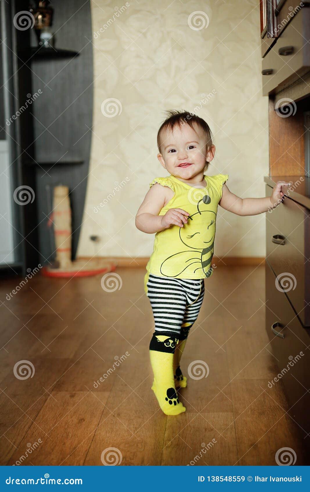 A filha da mãe pequena que levanta na roupa com um teste padrão de abelhas amarelas
