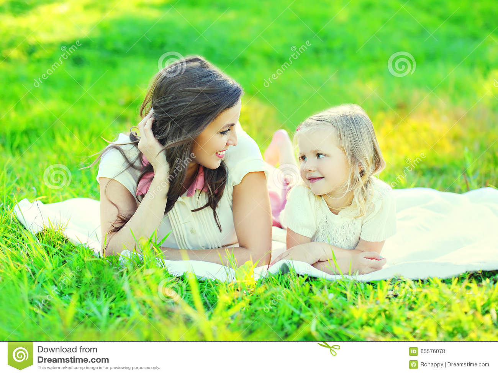 Filha de sorriso feliz da mãe e da criança que encontra-se junto na grama