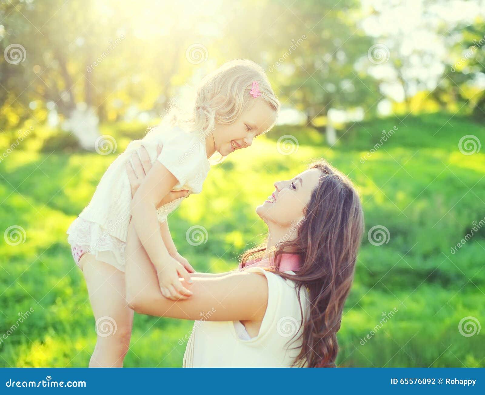 Filha de sorriso feliz da mãe e da criança que tem o divertimento