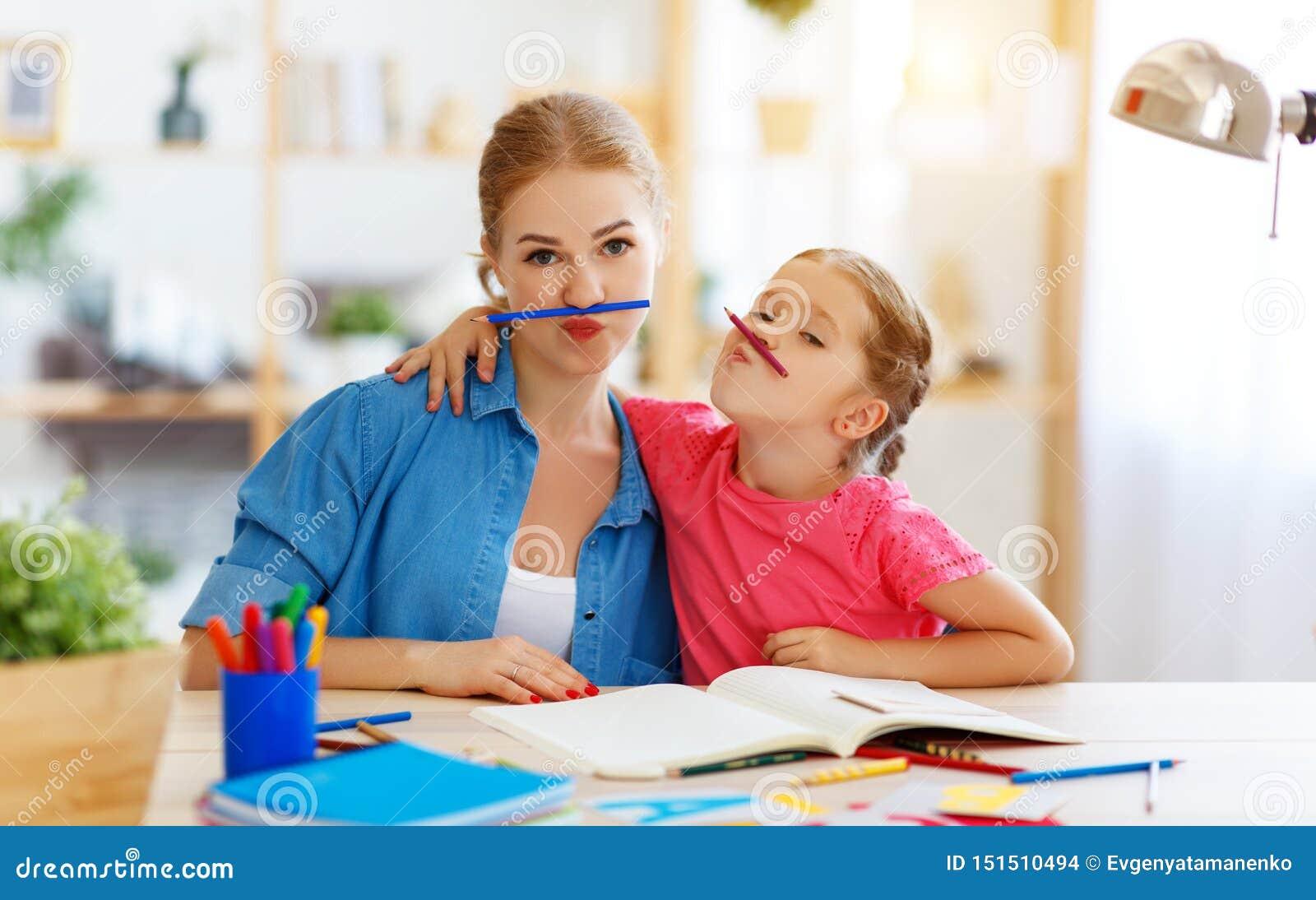Filha engraçada da mãe e da criança que faz a escrita e a leitura dos trabalhos de casa