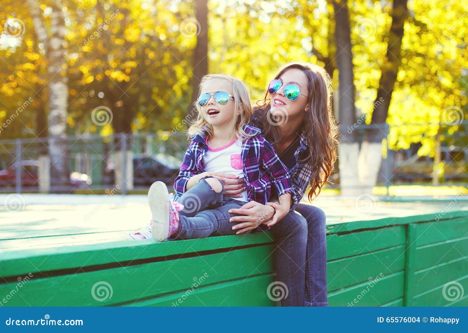 Filha feliz bonita da mãe e da criança que tem o divertimento junto na cidade