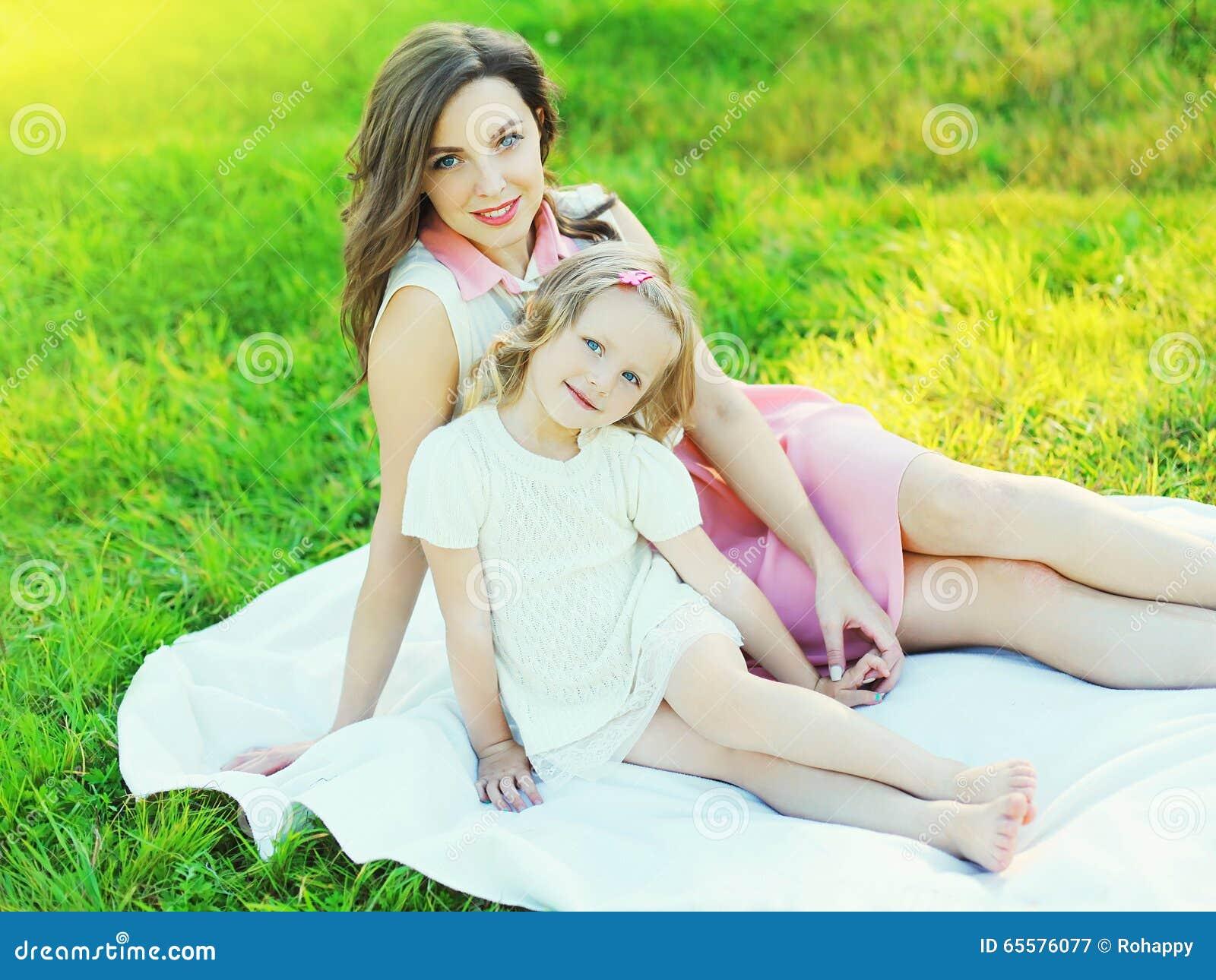 Filha feliz da mãe e da criança junto na grama