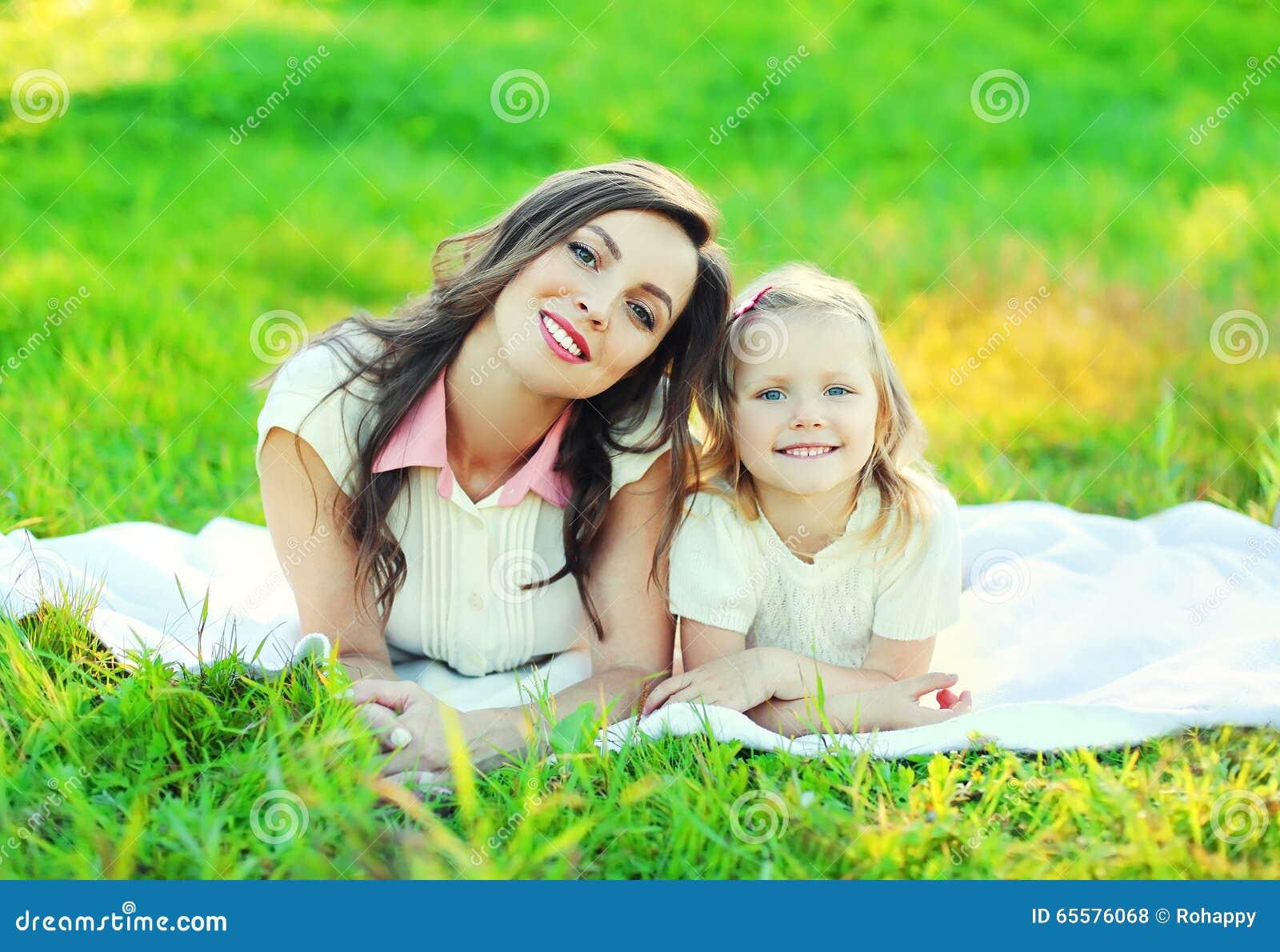 Filha feliz da mãe e da criança que encontra-se junto na grama no verão