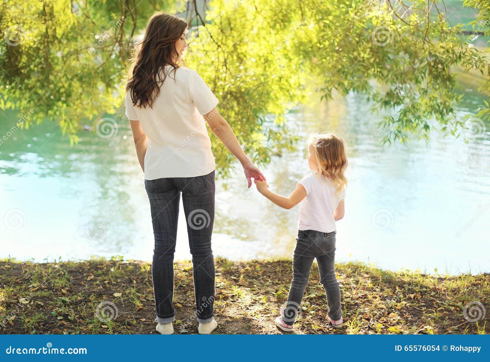 Filha feliz da mãe e da criança que mantém as mãos unidas no verão