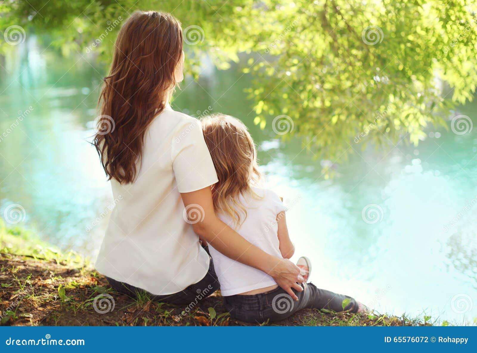 Filha feliz da mãe e da criança que senta-se junto no verão