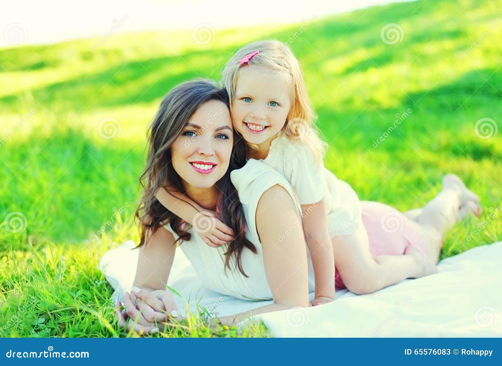 Filha nova feliz da mãe e da criança junto na grama no verão